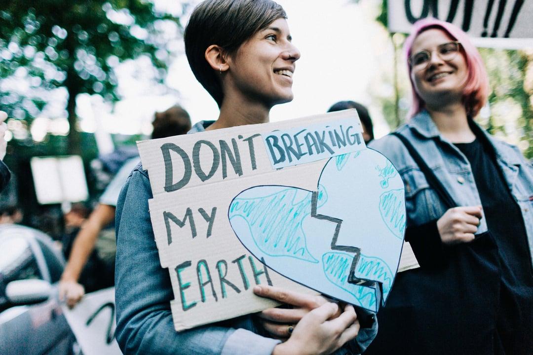 Frau mit Schild bei weltweitem Klimastreik