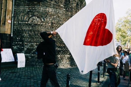 Mann mit Herz Flagge auf Fridays for Future Klimastreik