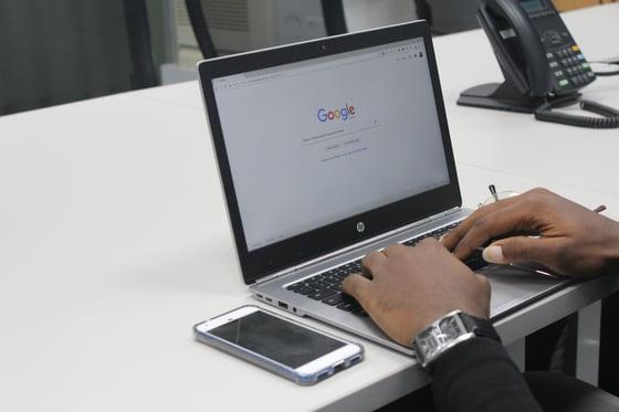 laptop steht auf tisch, hände auf tastatur, handy daneben