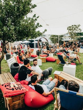 Wiese mit großer Menschenmenge, Stühlen, Sitzkissen und Tischen