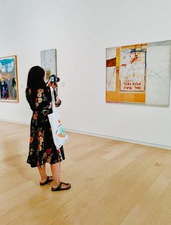 Frau steht vor Gemälde, fotografiert es