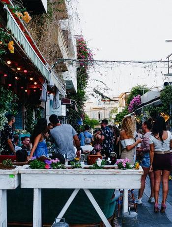 Straßen von Tel Aviv mit Lichterketten, Menschen, Tischen und Blumen
